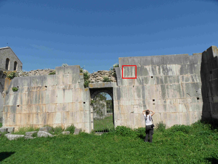 Team photographer standing in front of the Santissima Trinità wall, with the Hebrew tombstone (marked in red) several meters above her head.